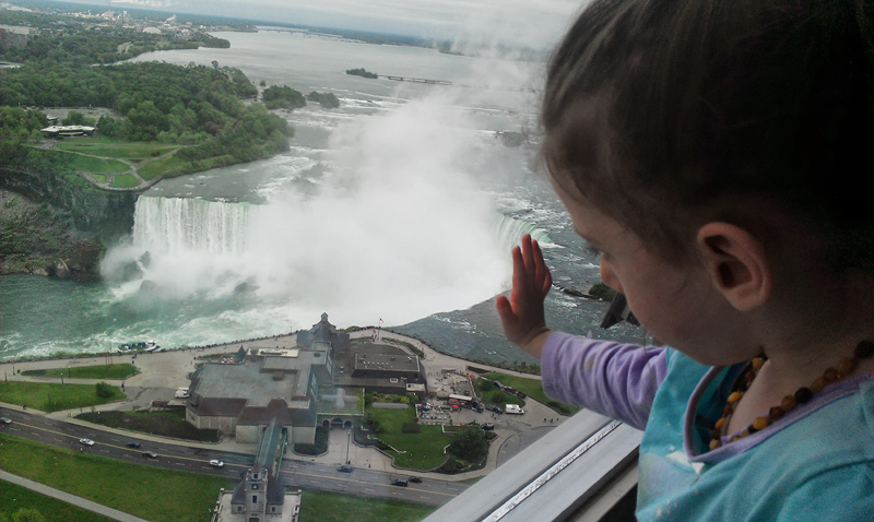 Tova looking at/touching the waterfall